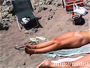 Spy webcam shot of a torrid nudist stunner tanning on the beach